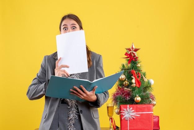 Widok z przodu szeroko-oczami młoda dziewczyna sprawdzanie dokumentów stojących w pobliżu drzewa xmas i koktajl prezenty