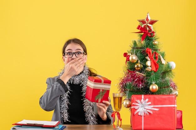 Widok z przodu szerokoooka dziewczyna w okularach siedzi przy stole oddając rękę