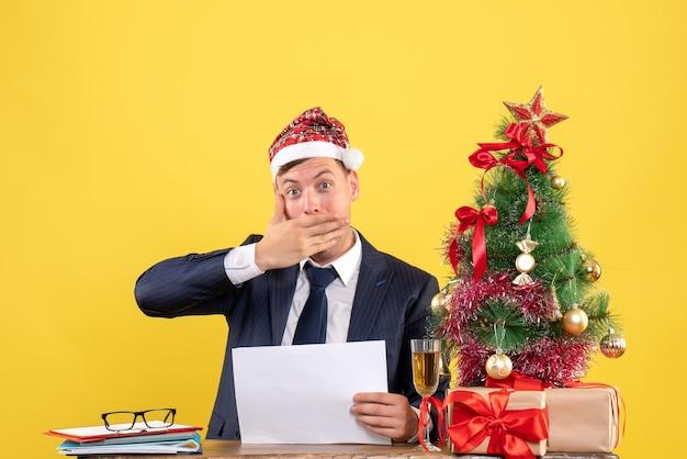 Widok z przodu szerokoookiego mężczyzny kładącego rękę na ustach siedzącego przy stole w pobliżu choinki i przedstawia na żółto