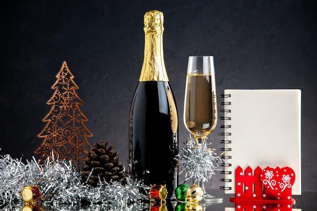 Widok z przodu szklana butelka szampana ozdoby świąteczne notatnik na ciemnej powierzchni