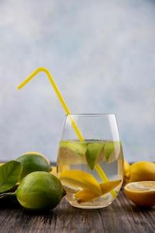 Widok z przodu szklanka wody z plasterkami cytryny z limonką i żółtą słomką
