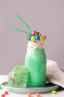 Widok z przodu szklanki deseru z kolorowych cukierków polewa i parasol