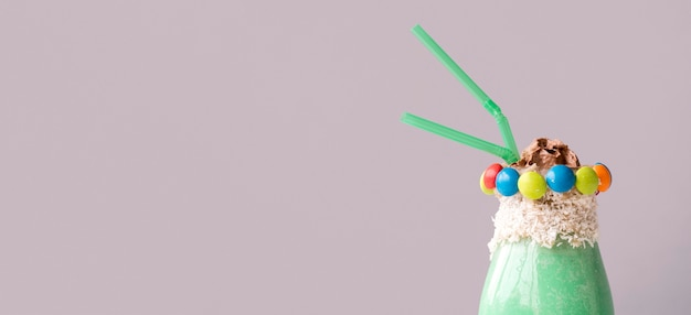 Widok z przodu szklanki deseru z kolorowych cukierków polewa i słomek