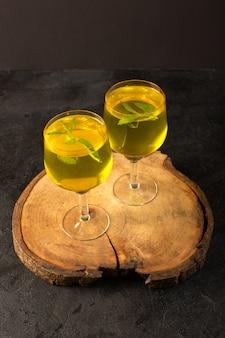 Widok z przodu szklanki z sokiem z cytryny w przezroczystych okularach na brązowym drewnianym biurku