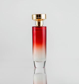 Widok z przodu szklany flakon perfum w czerwonym kolorze ze złotą plastikową osłoną