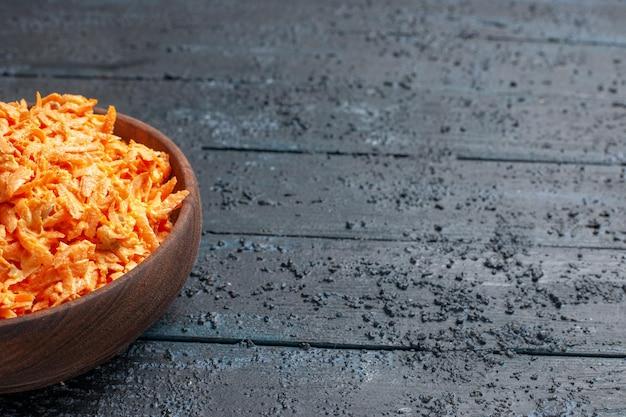 Widok z przodu tartej sałatki z marchwi wewnątrz talerza na ciemnoniebieskim rustykalnym biurku sałatka zdrowotna kolor dojrzałe warzywa dietetyczne