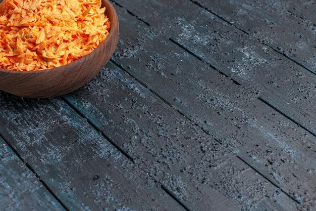 Widok z przodu tartej sałatki z marchwi wewnątrz talerza na ciemnoniebieskim rustykalnym biurku zdrowie sałatka kolor dojrzałe warzywa dietetyczne
