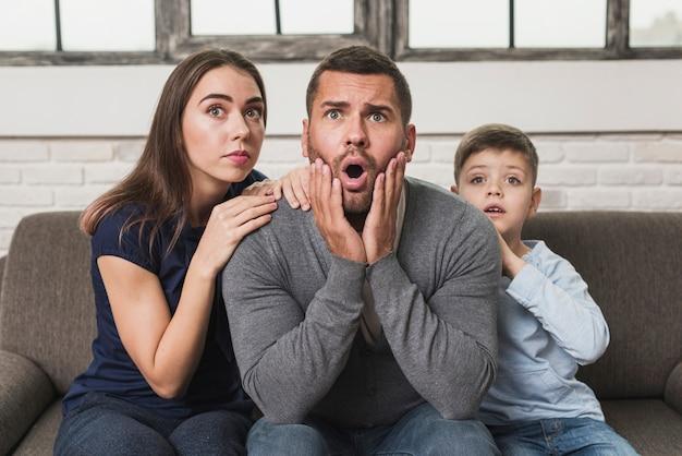 Widok z przodu tata ogląda telewizję z rodziną