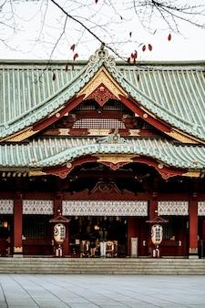 Widok z przodu tradycyjnej japońskiej drewnianej świątyni z dachem i latarniami