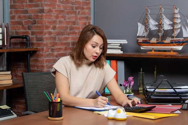 Widok z przodu transparentu z krótkimi włosami kobiety za pomocą kalkulatora siedzącego przy ścianie