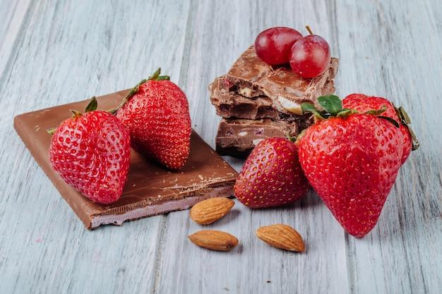 Widok z przodu truskawki z czekoladą i migdałami na szarej powierzchni