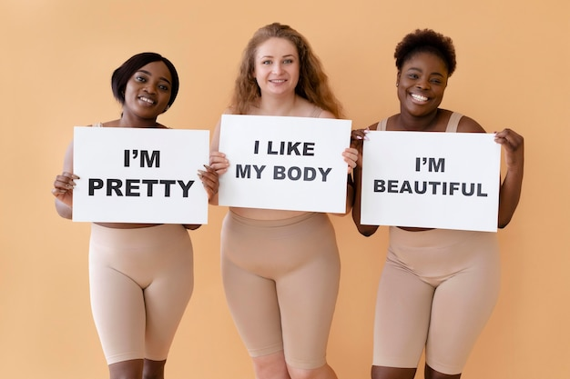 Widok z przodu trzech kobiet trzymających plakaty z informacją o pozytywnym nastawieniu do ciała