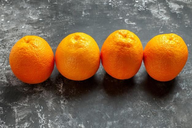Widok z przodu trzech naturalnych organicznych świeżych pomarańczy ustawionych w rzędzie na ciemnym tle