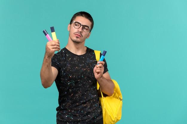 Widok z przodu ucznia w ciemnej koszulce żółty plecak trzymający kolorowe pisaki na niebieskiej ścianie