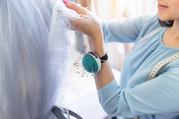 Widok z przodu udanego ślubu właściciela krawcowej pomiaru materiałów na manekin w biurze lub warsztacie.