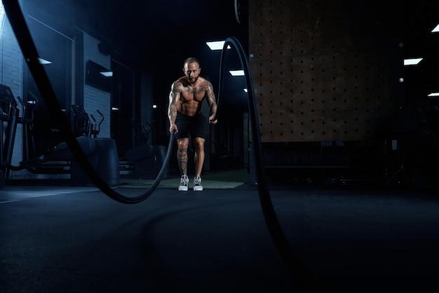 Widok z przodu umięśnionego bruneta robi trening liny bojowej w siłowni w ciemnej atmosferze.