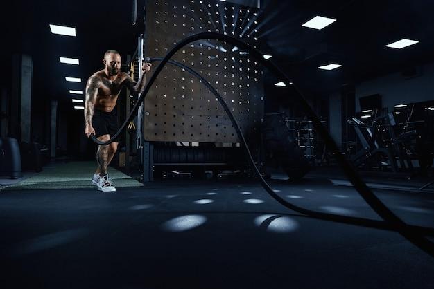 Widok z przodu umięśnionego brunetki bez koszuli robi trening liny bojowej w siłowni w ciemnej atmosferze.