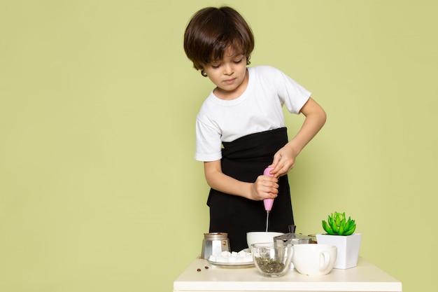 Widok z przodu urocza chłopiec śliczna w białej koszulce przygotowująca kawę na stole na kamiennej przestrzeni