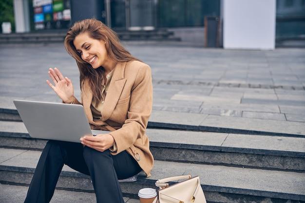 Widok z przodu uroczej młodej kobiety rasy kaukaskiej ze szczęśliwym uśmiechem komunikującej się przez skype