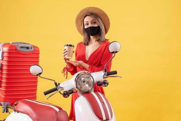 Widok z przodu uroczej młodej kobiety z czarną maską trzymającej filiżankę kawy w pobliżu motoroweru