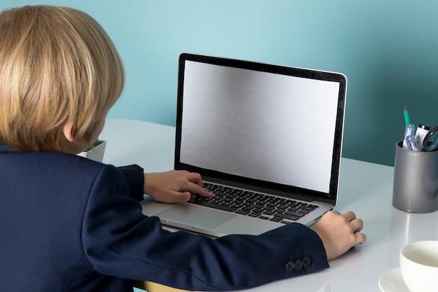 Widok z przodu uroczy chłopak w niebieskim klasycznym garniturze przed srebrną modą na laptopa