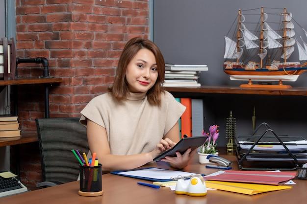 Widok z przodu uśmiechnięta kobieta korzystająca z kalkulatora siedzącego przy ścianie