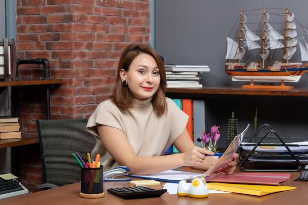 Widok z przodu uśmiechnięta kobieta siedząca przy ścianie