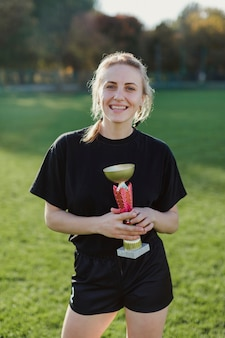 Widok z przodu uśmiechnięta kobieta trzyma trofeum