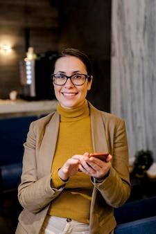 Widok z przodu uśmiechnięta kobieta trzymając telefon