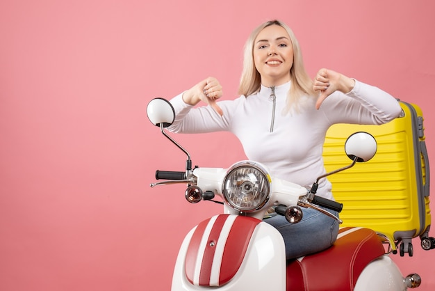 Widok z przodu uśmiechnięta młoda dama na motorowerze pokazując kciuk w dół znak