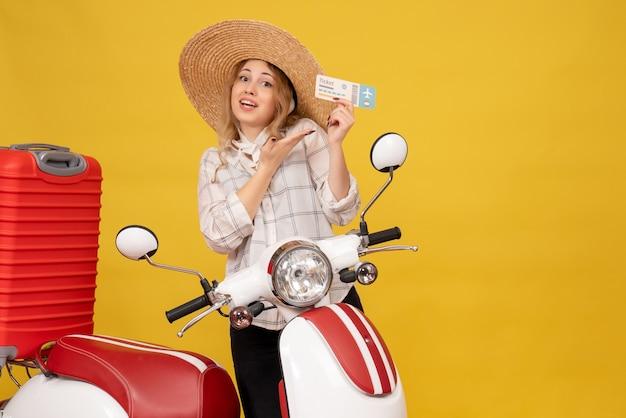 Widok z przodu uśmiechnięta młoda kobieta w kapeluszu, zbierając swój bagaż, siedząc na motocyklu i pokazując bilet