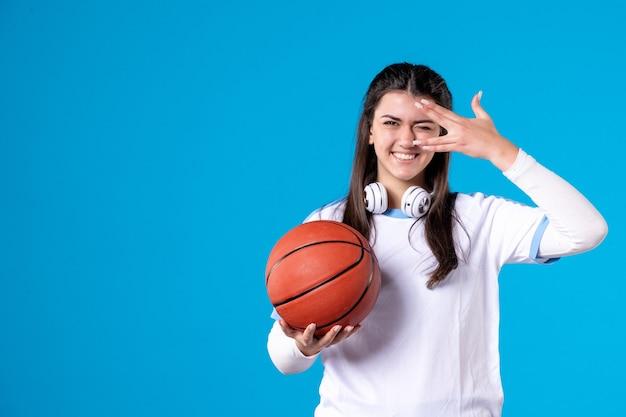 Widok z przodu uśmiechnięta młoda kobieta z koszykówką