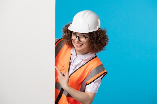 Widok z przodu uśmiechnięta żeński konstruktor w mundurze na niebiesko