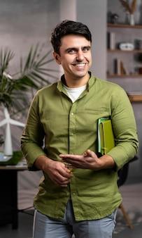 Widok z przodu uśmiechniętego człowieka obok przyjaznego dla środowiska układu projektu elektrowni wiatrowych