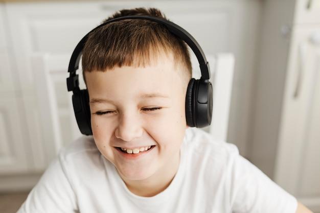 Widok z przodu uśmiechniętego dziecka noszącego słuchawki