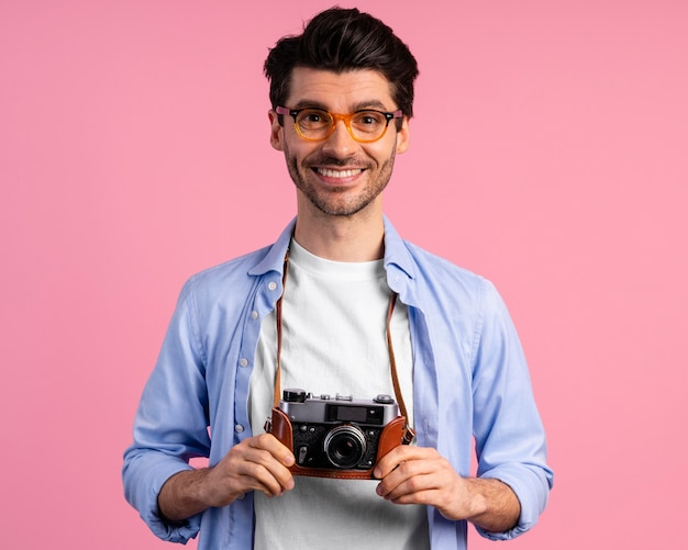 Widok z przodu uśmiechniętego fotografa płci męskiej z aparatem