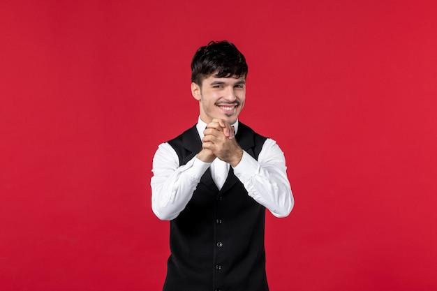 Widok z przodu uśmiechniętego kelnera męskiego w mundurze z motylem na szyi i szczęśliwym z powodu czegoś na czerwonym tle