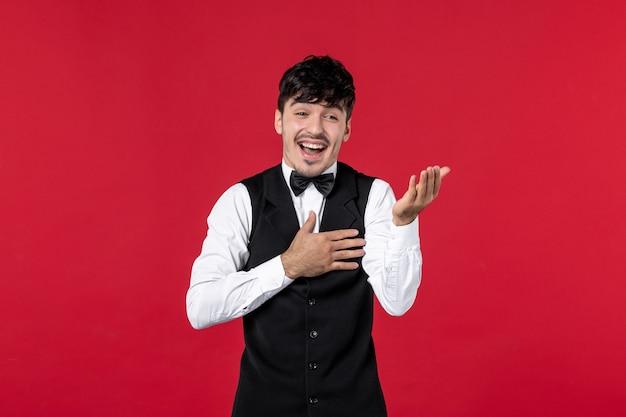 Widok z przodu uśmiechniętego kelnera męskiego w mundurze z motylem na szyi i zaciekawionym czymś na czerwonym tle