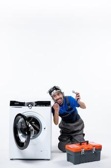 Widok z przodu uśmiechniętego mechanika trzymającego stetoskop siedzącego w pobliżu pralki na ścianie