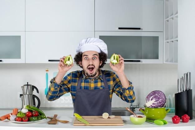 Widok z przodu uśmiechniętego męskiego szefa kuchni ze świeżymi warzywami i gotującego za pomocą narzędzi kuchennych oraz pokazującego pokrojoną zieloną paprykę w białej kuchni