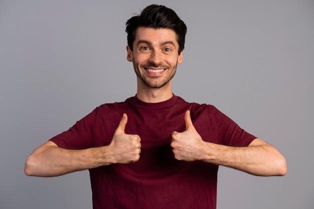 Widok z przodu uśmiechniętego mężczyzny pokazującego kciuki do góry