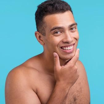Widok z przodu uśmiechniętego mężczyzny, pokazującego swoją czysto ogoloną twarz