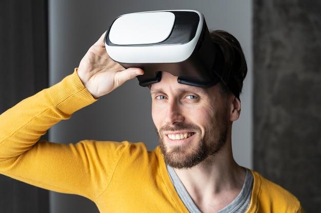 Widok z przodu uśmiechniętego mężczyzny pozującego z zestawem słuchawkowym wirtualnej rzeczywistości