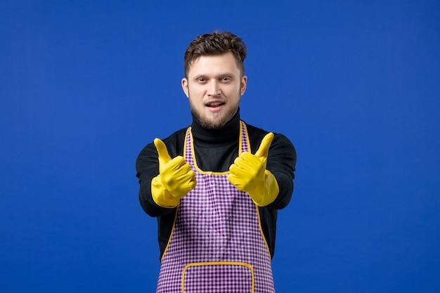 Widok z przodu uśmiechniętego młodego mężczyzny, który robi kciuk w górę, znak stojący na niebieskiej ścianie