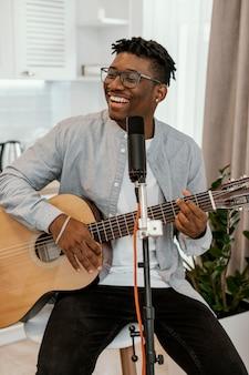 Widok z przodu uśmiechniętego muzyka płci męskiej w domu, grając na gitarze i śpiewając