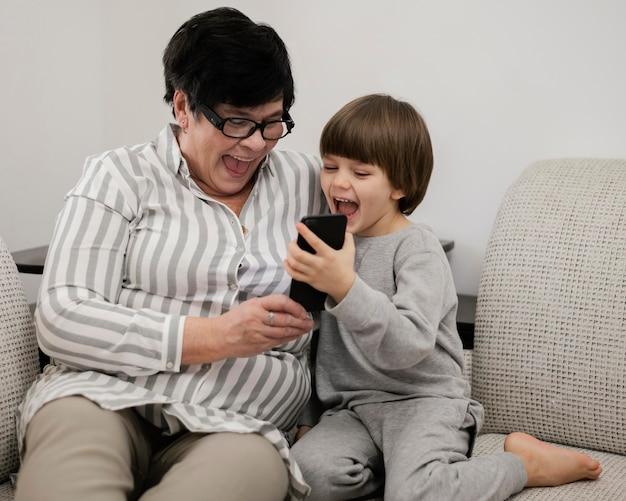 Widok z przodu uśmiechniętego wnuka i babci razem patrząc na smartfona