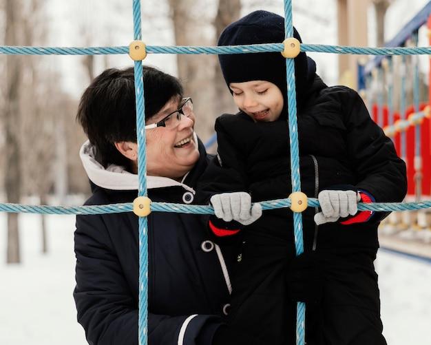 Widok z przodu uśmiechniętej babci i wnuka na zewnątrz w zimie w parku