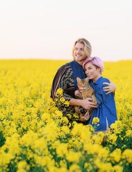 Widok z przodu uśmiechniętej dziewczyny ze swoim chłopakiem, stojącej wśród pola z kotem i odwracającej wzrok