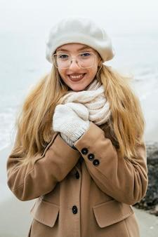 Widok z przodu uśmiechniętej kobiety na zewnątrz na plaży w zimie