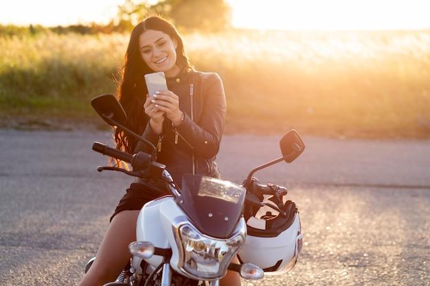 Widok z przodu uśmiechniętej kobiety patrząc na smartfona siedząc na swoim motocyklu